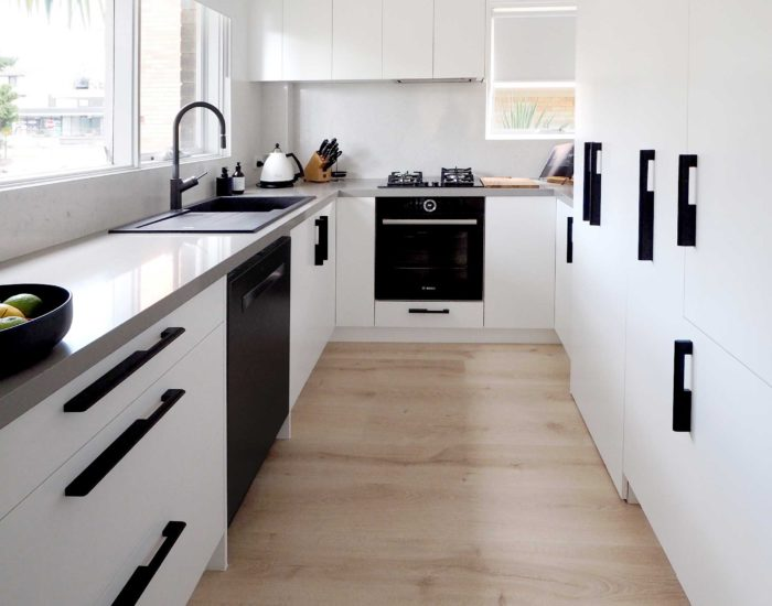 Small kitchen renovation sydney with white cupboards and matt black handles